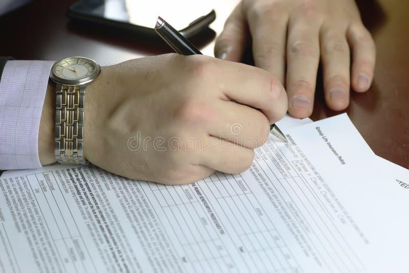 Ręka podpisujący ubezpieczenie obraz stock