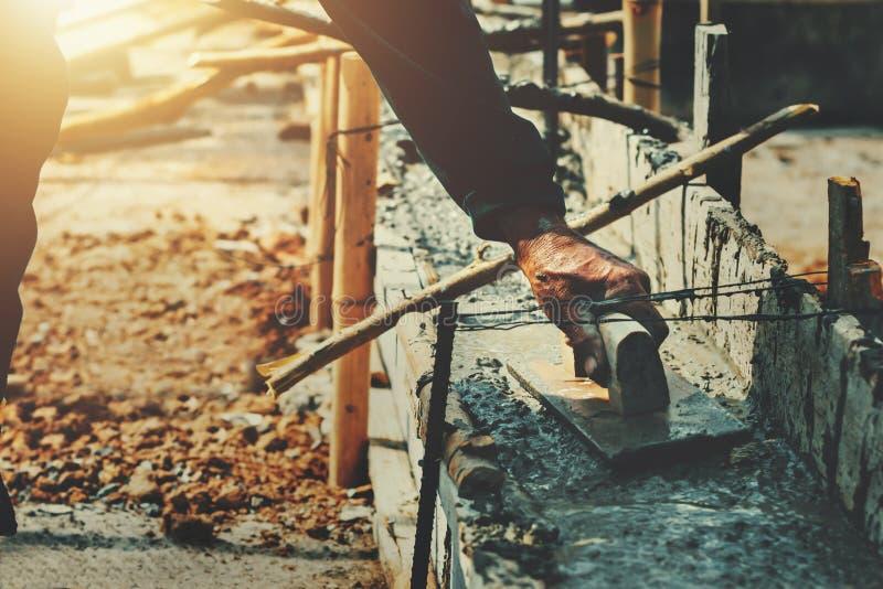 ręka pracownika niwelacyjny beton dla mieszanka cementu przy budową obraz royalty free