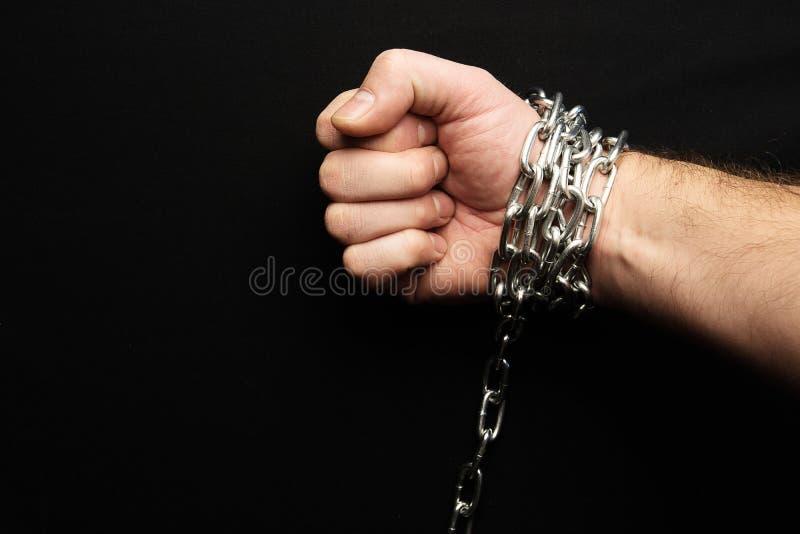 Ręka przykuwająca na czarnym tle, srebny metalu łańcuch zdjęcie royalty free