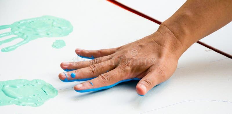 Ręka robi śladowi kolorowemu symbolowi na białego papieru tle obraz royalty free