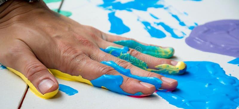 Ręka robi śladowi kolorowemu symbolowi na białego papieru tle obraz stock