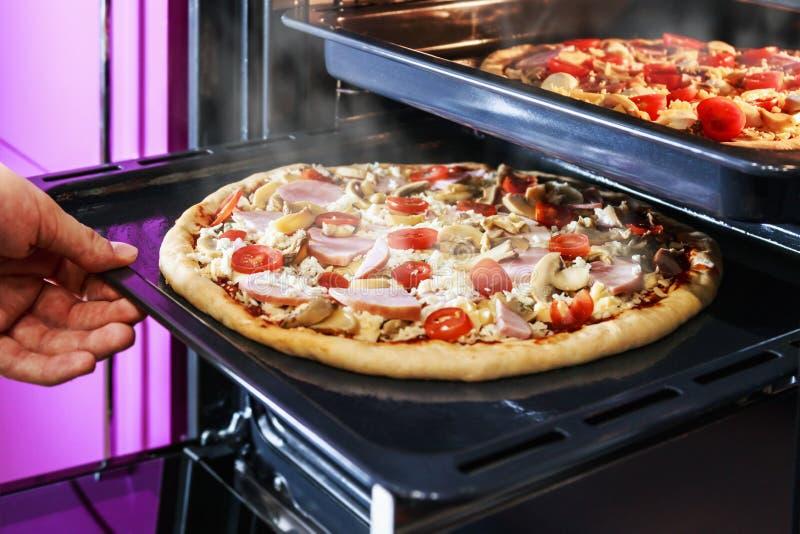 Ręka rusza się tacę pizza z pieczarkami, baleronem i mozzarellą, zdjęcie stock