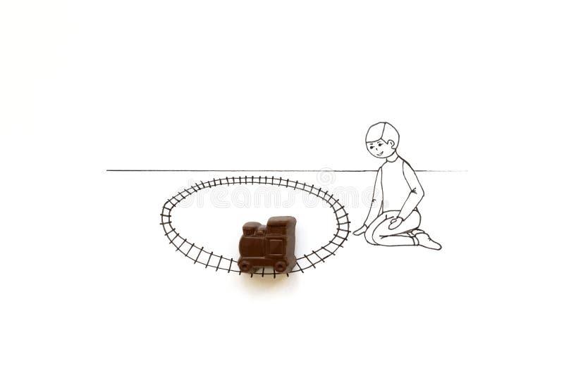 Ręka rysuje ślicznego kreskówki dziecka bawić się z czekolada pociągu zabawką Minimalny, kreatywnie lub karmowy sztuki pojęcie, k zdjęcie royalty free
