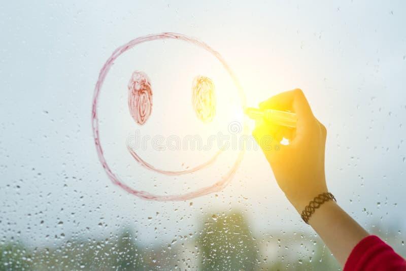 Ręka rysuje pozytywnego śmiesznego smiley na dżdżystym jesieni okno obraz royalty free