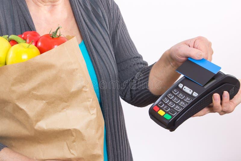 Ręka starsza kobieta używa płatniczego terminal z contactless kredytową kartą, płaci dla robić zakupy zdjęcia stock
