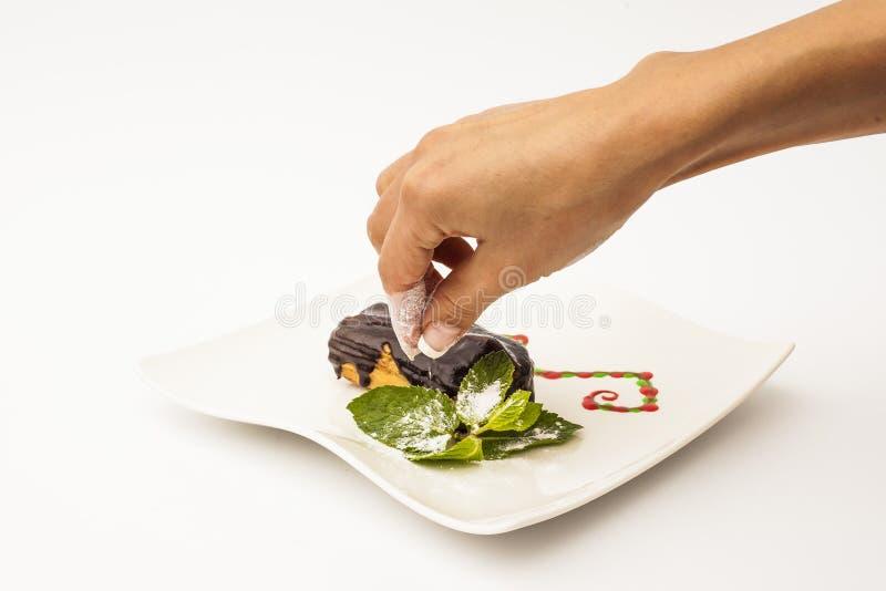 Ręka stawia niektóre cukier na Eclair torcie z czekoladą na bielu talerzu z mennicą na białym tle zdjęcie royalty free