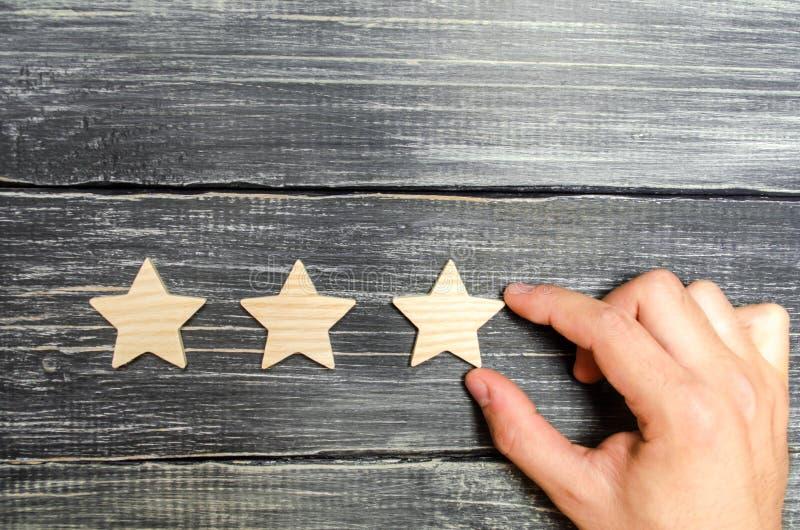 Ręka stawia trzeci gwiazdę pojęcie sukces i rozpoznanie, podnoszący prestiż i ocenę Przemiana nowy poziom Busi zdjęcie royalty free