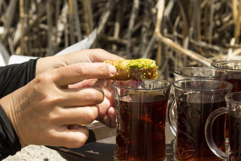 Ręka stawia wschodnią słodkość w szkle czarna herbata, w górę obraz stock