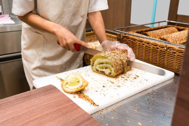 Ręka szef kuchni zielonej herbaty tnący chleb na białej desce obraz stock