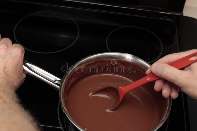 Ręka Trzyma łyżki i niecki Porywającego kakao Mieszającego z wodą obraz royalty free
