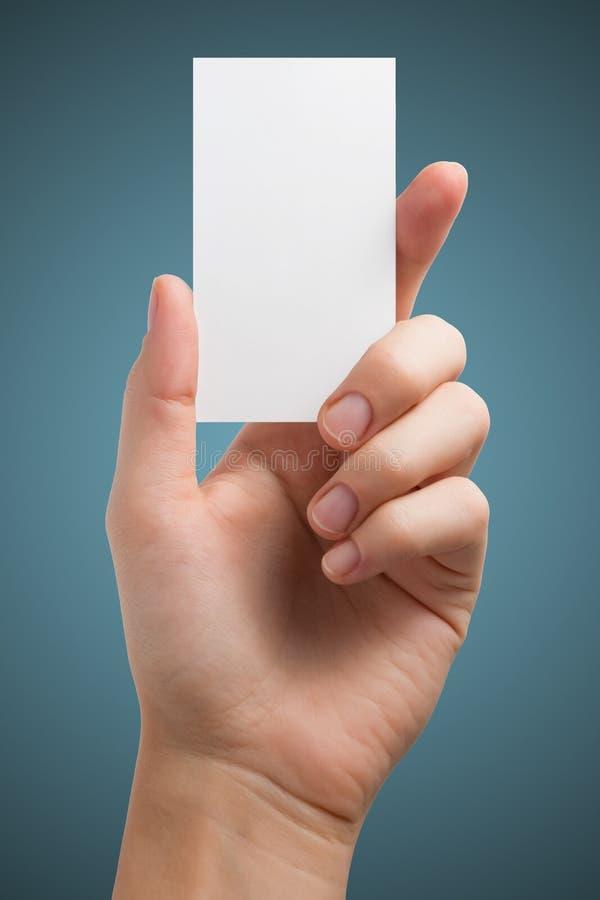 Ręka trzyma białą pustą biznesową wizyty kartę, prezent, bilet, przepustka, przedstawia odosobnionego na błękitnym tle Kopiuje pr obrazy stock