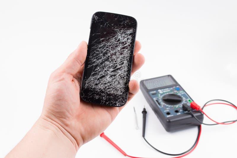 Ręka trzyma czarnego telefon komórkowego z łamanym ekranem na białym tle fotografia stock