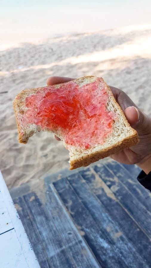 Ręka trzyma kąsek grzankę z truskawkowym ignamem obok piaska był zdjęcie stock