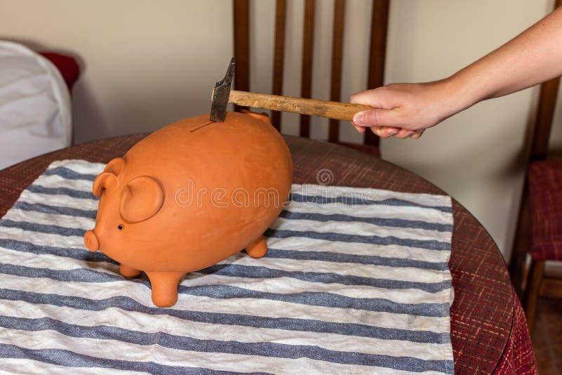 Ręka trzyma młot na brązu prosiątka banku na stole obrazy stock