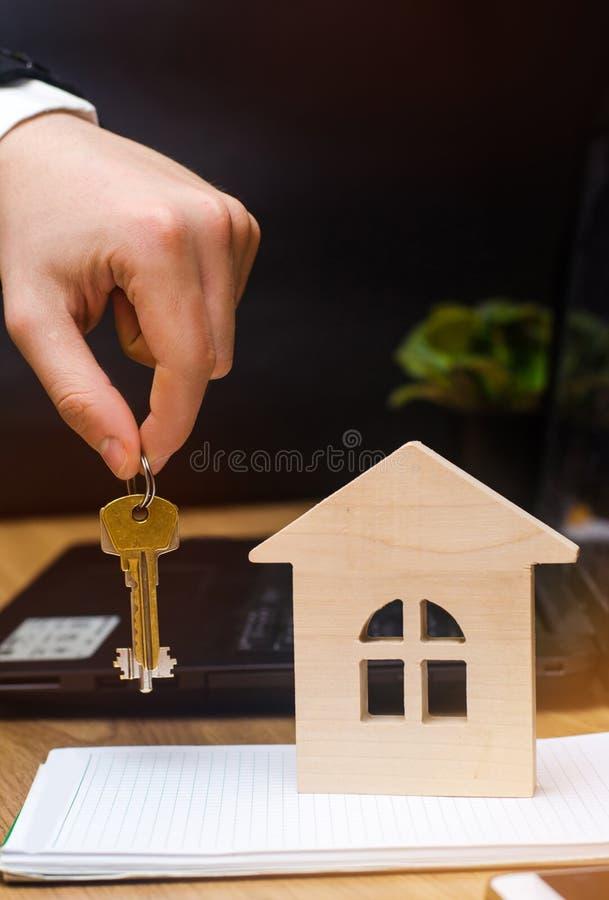 Ręka trzyma modela dom i klucze nieruchomości buyi zdjęcia royalty free