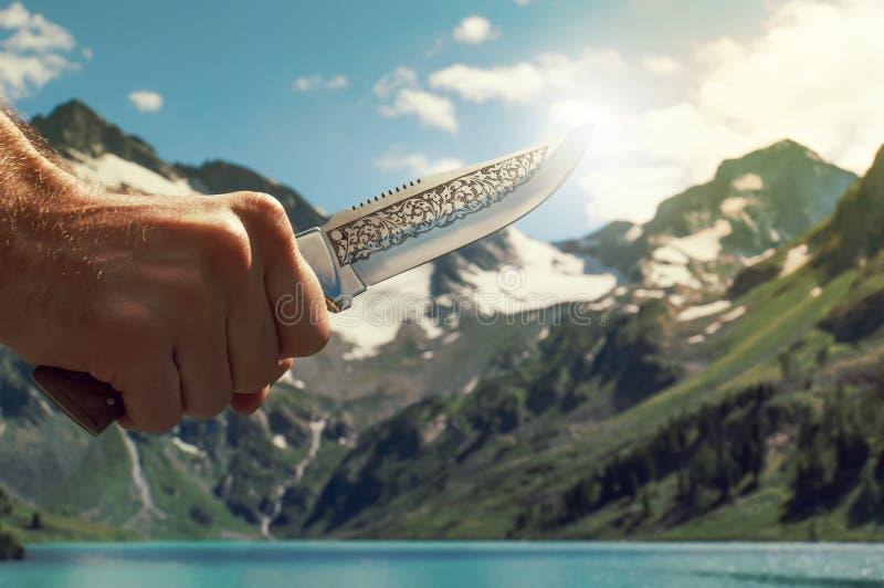 Ręka trzyma nóż Przeciw jaskrawej słońca i góry scenerii fotografia royalty free