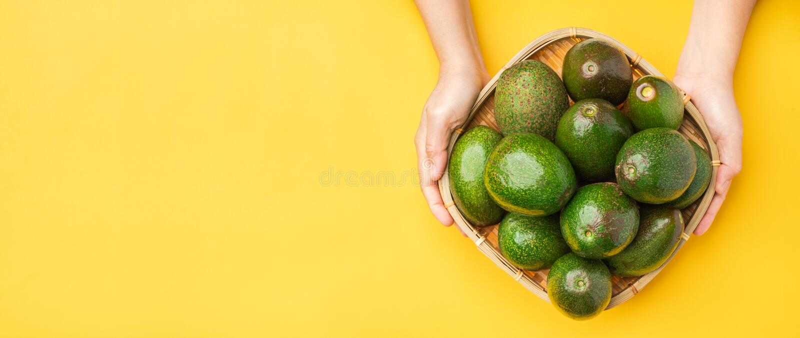 Ręka trzyma organicznie avocados całą owoc w koszu na koloru żółtego stołu tle Zdrowi super foods dla diety Świeży warzywo od obrazy stock