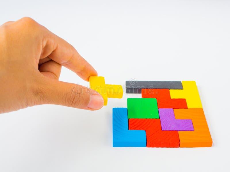 Ręka trzyma ostatniego kawałek uzupełniać kwadratowej tangram łamigłówki kolorową drewnianą łamigłówkę dla dzieciaka na białym tl obraz royalty free