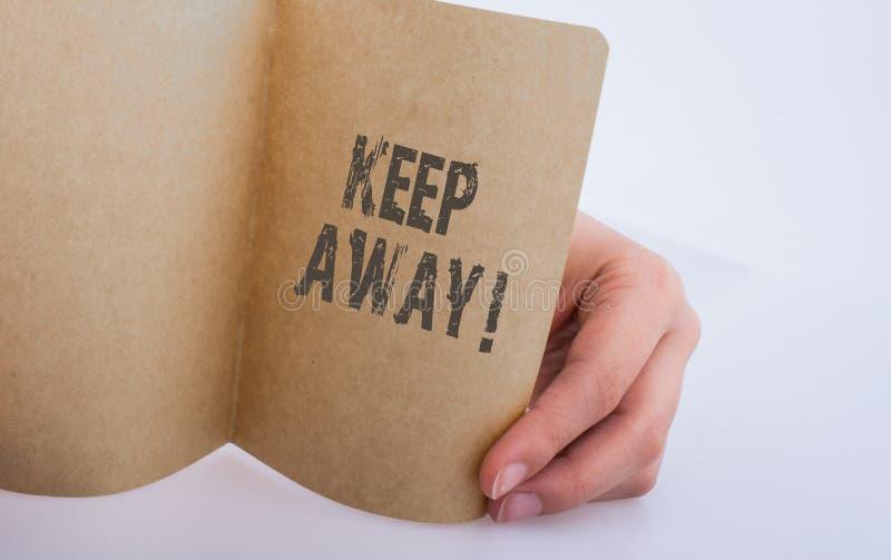 Ręka trzyma papierowego pisze utrzymanie daleko od obraz royalty free