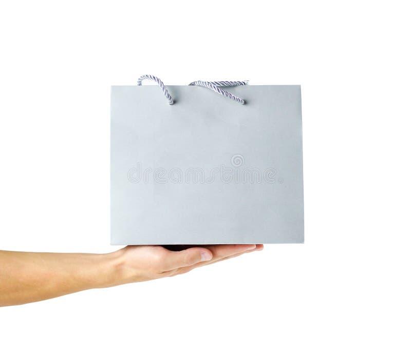Ręka trzyma piękną prezent szarość torbę z bliska pojedynczy białe tło zdjęcia royalty free