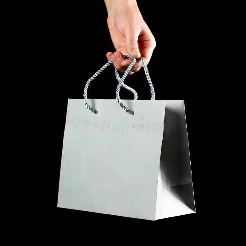 Ręka trzyma piękną prezent torbę z bliska Odizolowywający na czarny tle zdjęcia royalty free