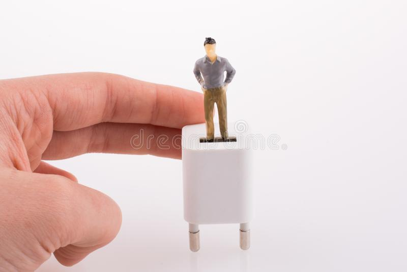 Ręka trzyma postać na adaptatorze obraz stock