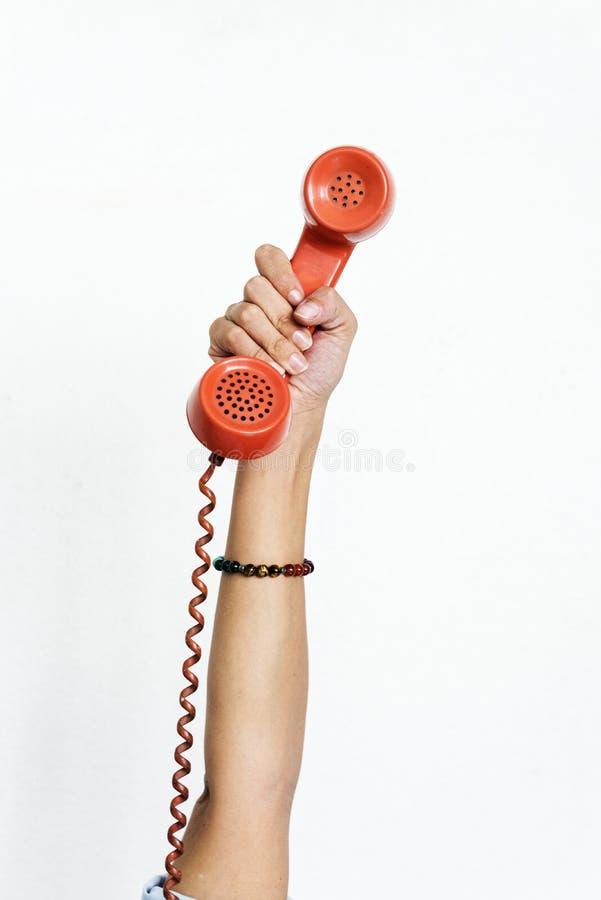 Ręka trzyma retro telefon odizolowywający na bielu obraz royalty free