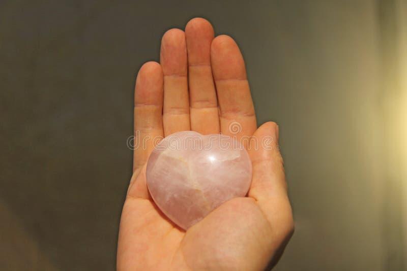 Ręka trzyma serce naturalna kamień menchii kwarc Serce w brzęczeniach zdjęcia royalty free