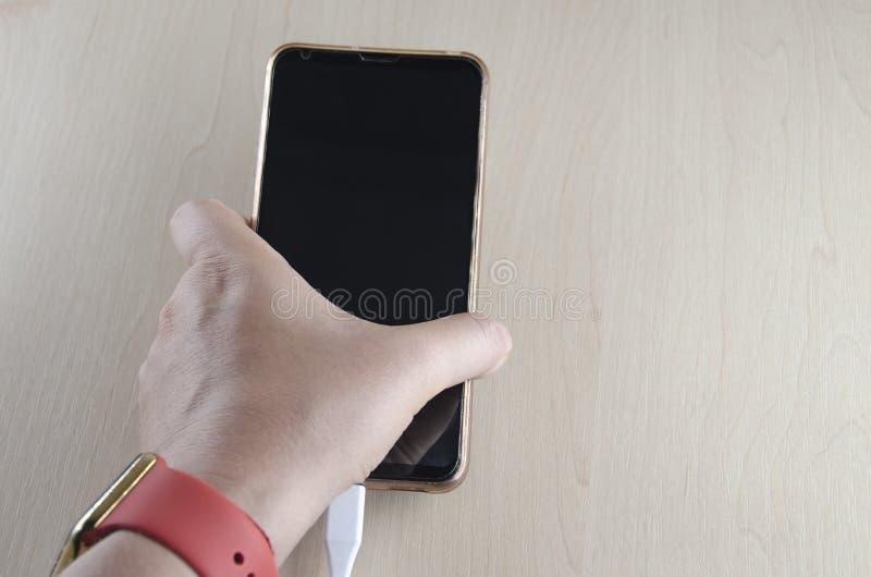 Ręka trzyma smartphone dalej podładowywa na lekkim tle obrazy royalty free