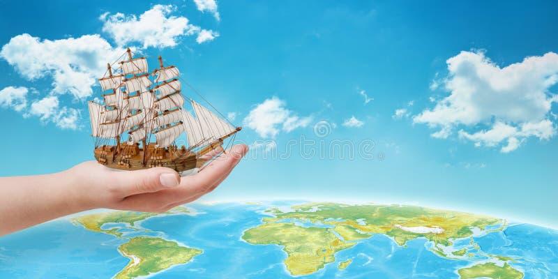 Ręka trzyma statek nad kulą ziemską Pojęcie podróżować przez morze fotografia royalty free