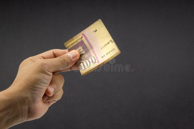Ręka trzyma sto MACEDONIA walut, Macedoński denaru banknot na czarnym tle fotografia stock