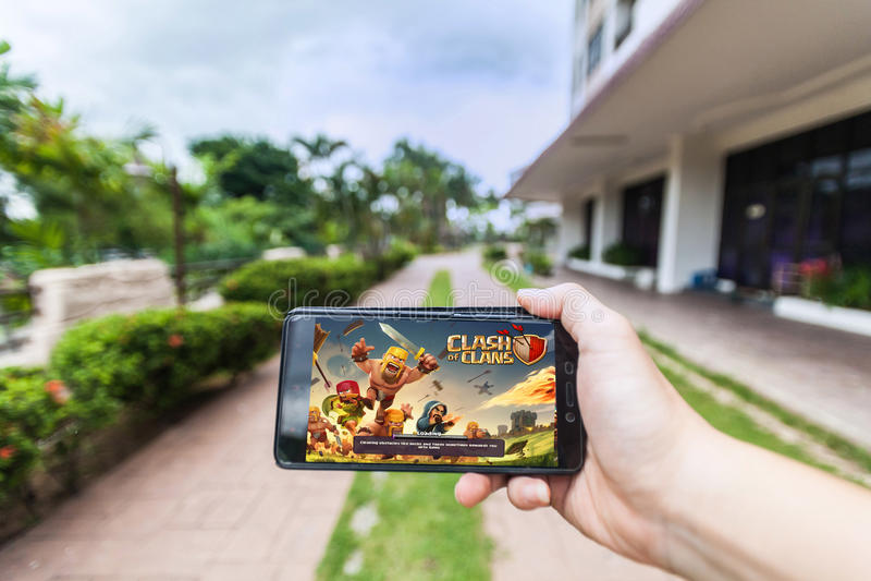 Ręka trzyma telefon komórkowego bawić się Supercell ` s zderzenie klan fotografia royalty free