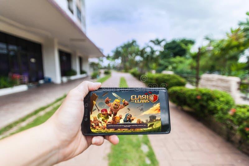 Ręka trzyma telefon komórkowego bawić się Supercell ` s zderzenie klan obraz royalty free