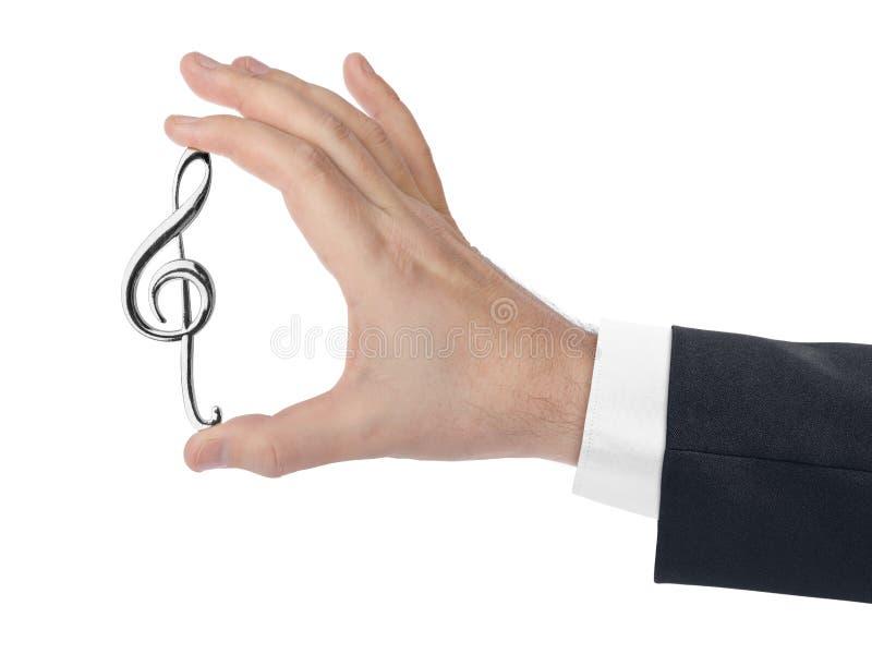 Ręka trzyma treble clef zdjęcie stock