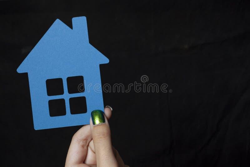Ręka trzyma troszkę błękitnego papieru dom zdjęcie royalty free