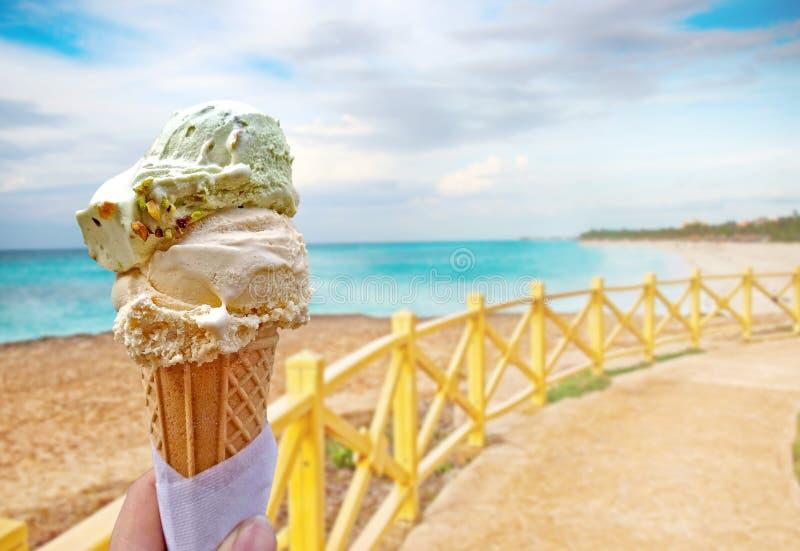 Ręka trzyma waniliowego lody To lokalizuje w tropikalnym kurorcie w Karaiby fotografia royalty free