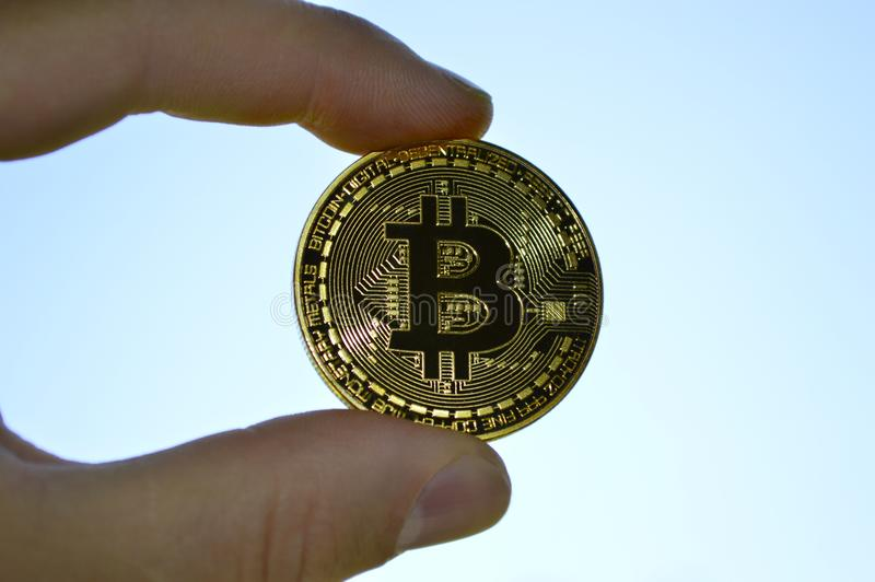 Ręka trzyma złocistą monetę Bitcoin zdjęcia stock