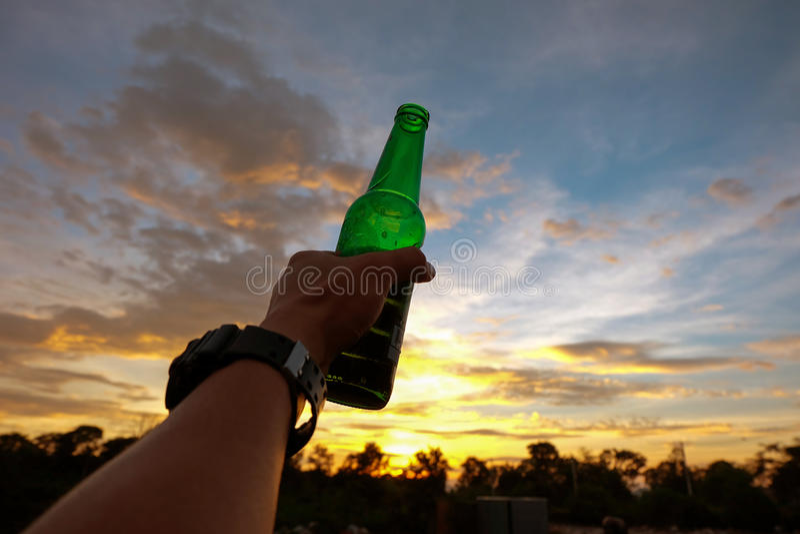 Ręka trzyma zieloną piwną butelkę mężczyzna obraz stock
