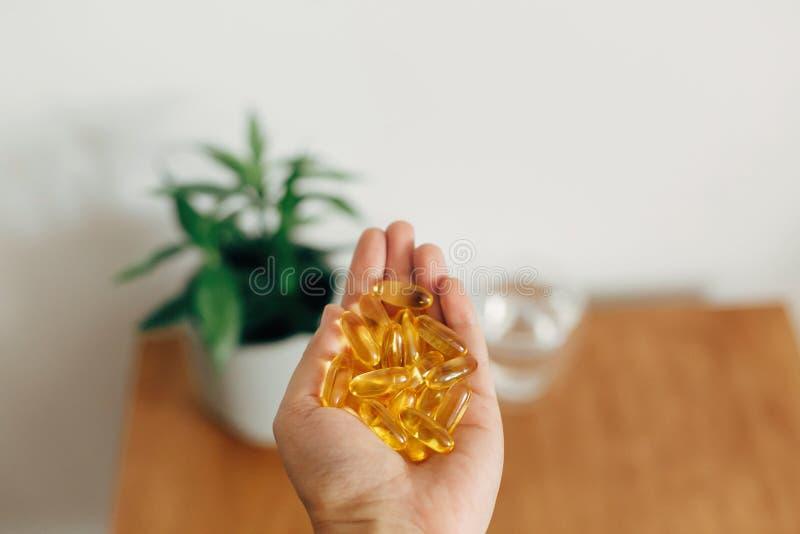 Ręka trzymająca omega 3 kapsułki nad drewnianym stołem ze szklanką wody Dawka poranna witaminy Olej rybny w tabletkach Pomoc zdro obraz stock