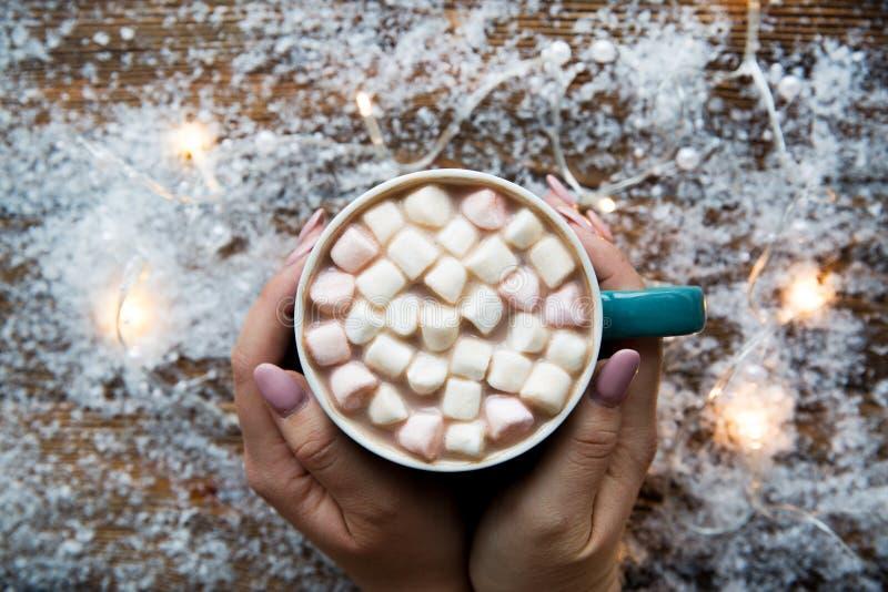 Ręka trzymająca smaczne gorące kakao z pianką na śnieżnym jasnym tle zdjęcia royalty free