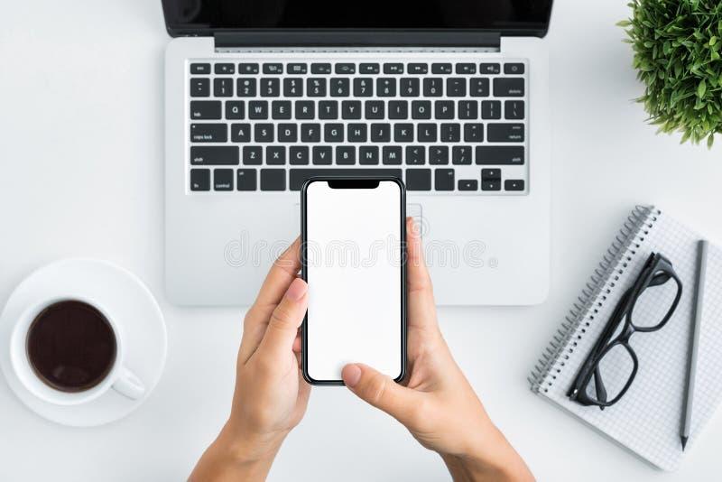 Ręka używać smartphone na białym drewnianym tle zdjęcie royalty free