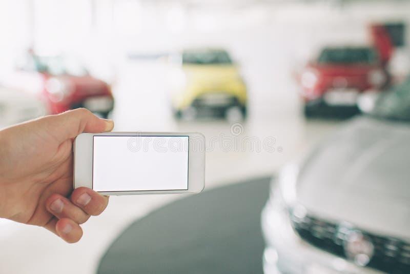 Ręka używać telefonu bielu ekran Samochodowe sprzedaże, rynek Samochód sala wystawowa obrazy royalty free