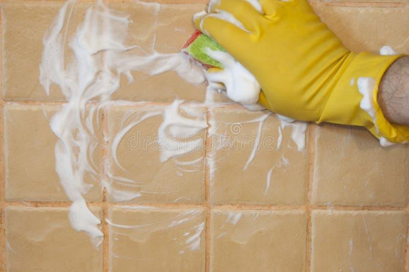 Ręka w żółtych rękawiczkach z gąbką myje płytkę cleaning pojęcia dishwashing ciecza gąbki zdjęcie royalty free