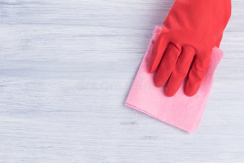 Ręka w czerwonej gumowej rękawiczce wyciera stołową powierzchnię z łachmanem obrazy royalty free