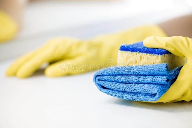 Ręka w gumowej żółtej rękawiczkowej mienie gąbce fotografia royalty free