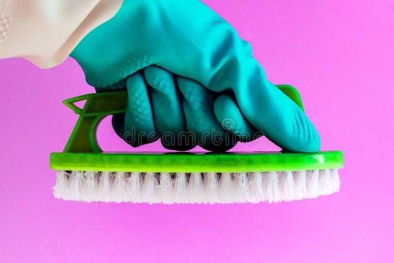 Ręka w gumowej lateksowej rękawiczce z Handheld podłogowym muśnięciem czyści wewnątrz na różowym tle obrazy royalty free