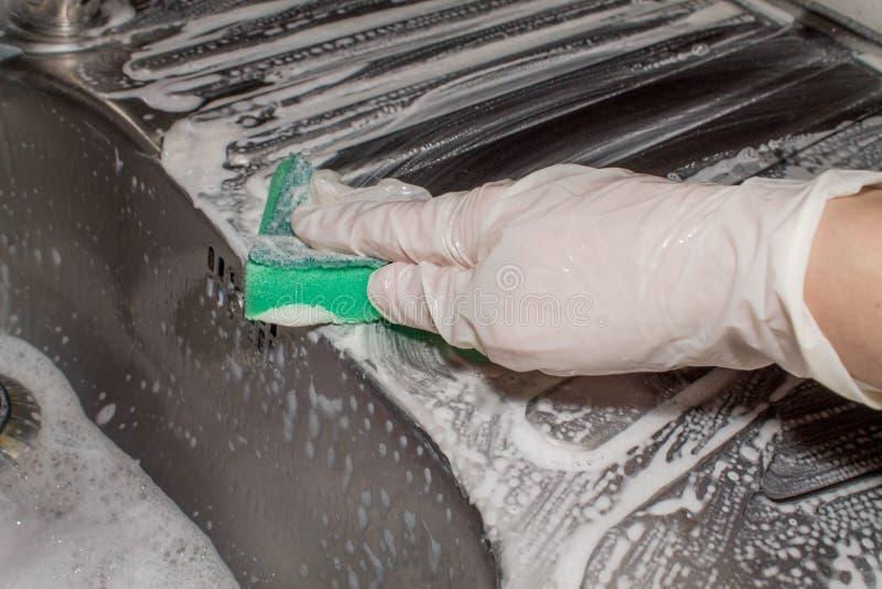 Ręka w lateksowym rękawiczkowym duster myje metalu zlew cleaning zdjęcia royalty free