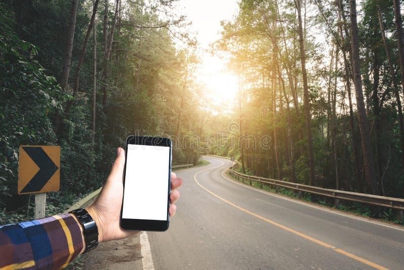 Ręka w modnisia koszulowego mienia pustym smartphone z lasem i f zdjęcia stock
