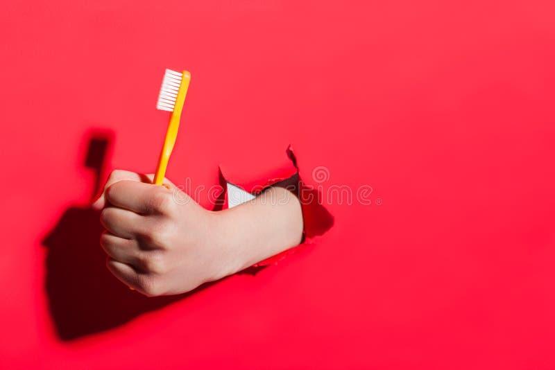 Ręka w poszarpanym papierowego mienia toothbrush fotografia stock