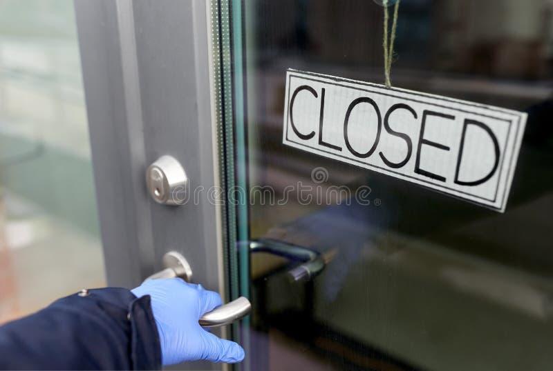 Ręka w rękawicy medycznej trzymająca się za zamknięte drzwi fotografia stock